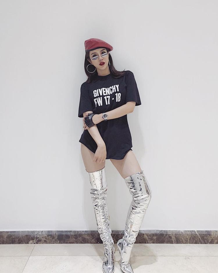 Áo thun dáng dài theo style giấu quần phối cùng boots ánh bạc là sự chọn lựa của Diệp Lâm Anh khi xuống phố. Cô nàng cũng không quên mang thêm mũ nồi và mắt kính tin hin nhằm hoàn chỉnh set đồ thời thượng.