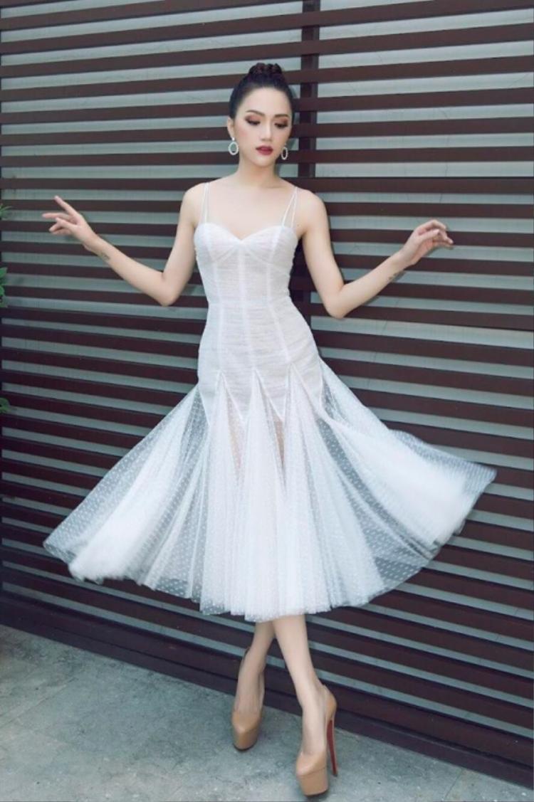 Chiếc váy trắng đơn giản vô cùng hợp với nét đẹp quyến rũ của Hương Giang. Hoa hậu Chuyển giới Quốc tế 2018 khiến người đối diện không thể rời mắt khi khoe khéo làn da trắng ngần cùng vóc dáng chuẩn trong trang phục ôm cơ thể nhưng không hề phô phang. Với thiết kế xòe đã quá nổi bật, nàng hậu chỉ để kiểu tóc bới cao đơn giản, tôn lên khuôn mặt trái xoan dễ nhìn.