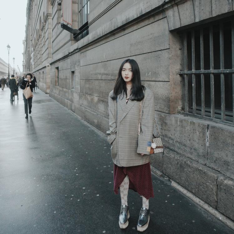 Cùng chọn vest vai to dáng freesize, nhưng Châu Bùi lại sử dụng đôi giày đế bánh mì màu bạc cùng đôi vớ cao cổ của Gucci làm điểm nhấn khi thả dáng trên đường phố Paris.