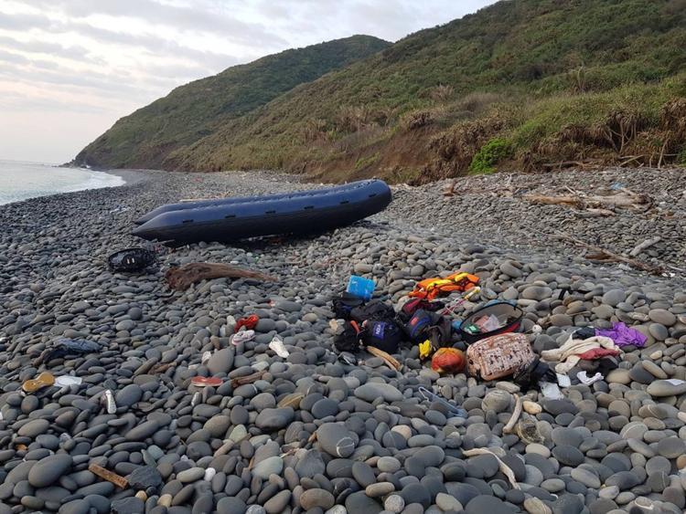 Hành lý của những người di cư bất hợp pháp và xuồng cứu sinh trôi dạt vào bờ biển. Ảnh:CGA