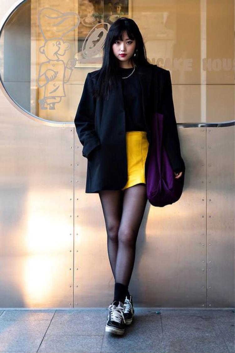 Tín đồ thời trang này thể hiện chất riêng bằng việc hoà phối mẫu chân váy da sắc vàng cùng blazer độn vai phom dáng oversized khi xuống phố.