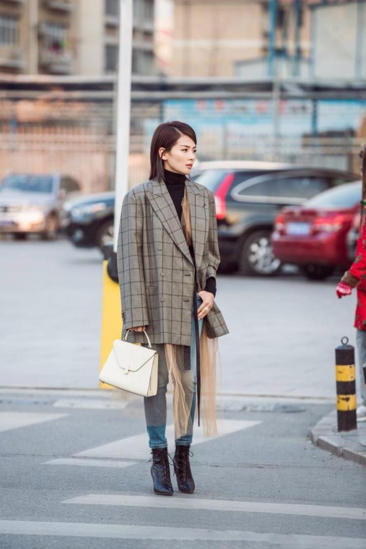 Nữ diễn viên Lưu Đào cũng có bộ đồ ấn tượng với áo blazer kẻ độn vai kiểu dáng oversized rộng rãi. Cô mặc với quần jeans và boots cao buộc dây, dải khăn voan khiến set đồ bớt cứng nhắc.