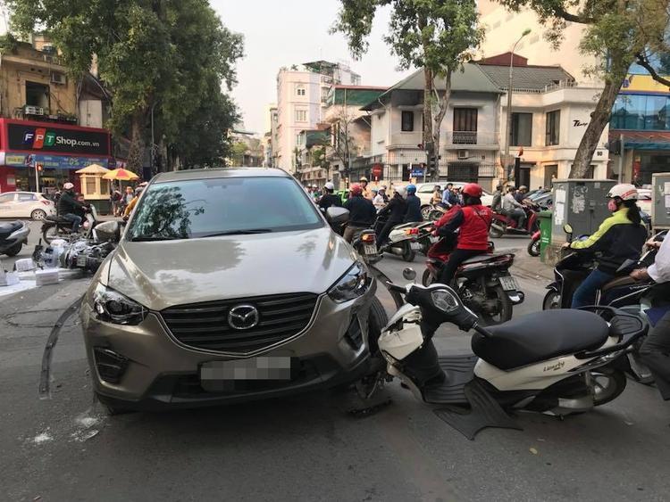 Một chiếc xe máy hư hỏng mắc vào ô tô.