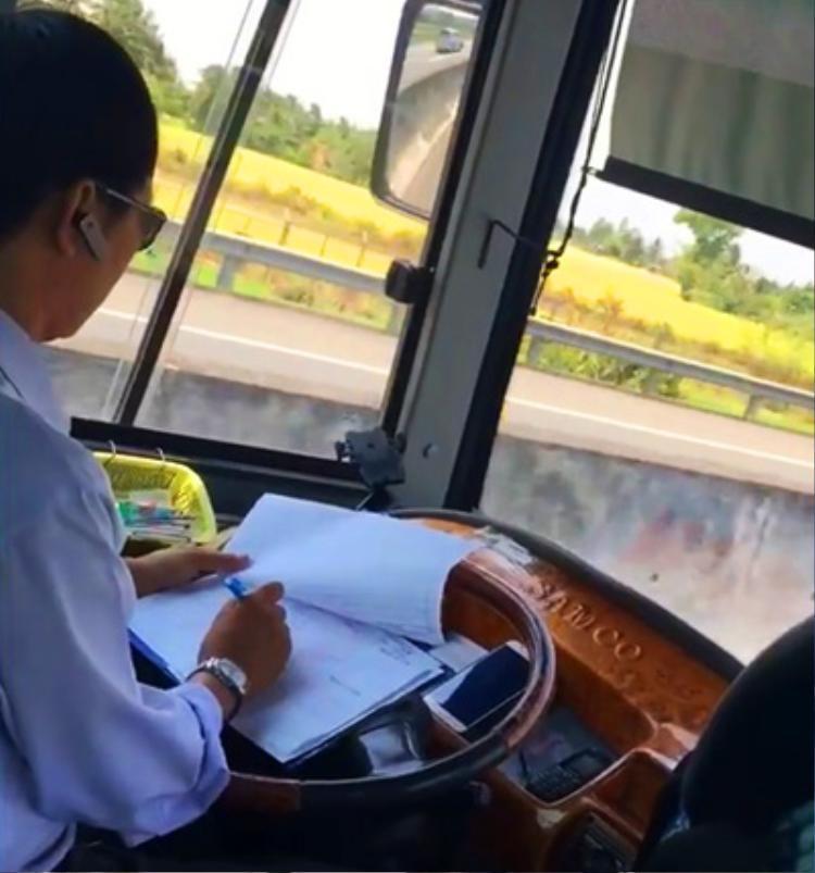Tài xế ghi chép khi đang lái xe. Ảnh cắt từ clip.