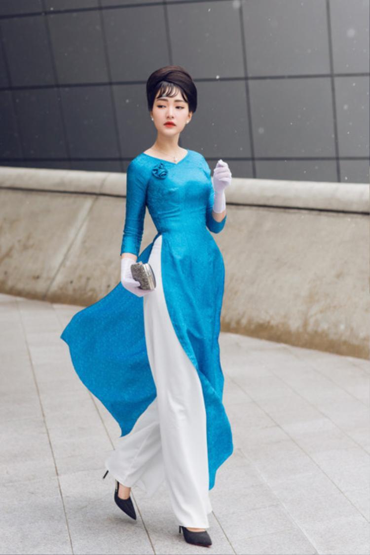 Khác với vẻ đẹp dịu dàng nữ tính trước đó, Ngọc Trân trở nên kiêu kỳ, quý phái khi diện hai thiết kế áo dài lụa tơ tằm và lãnh Mỹ A của NTK Tùng Vũ.