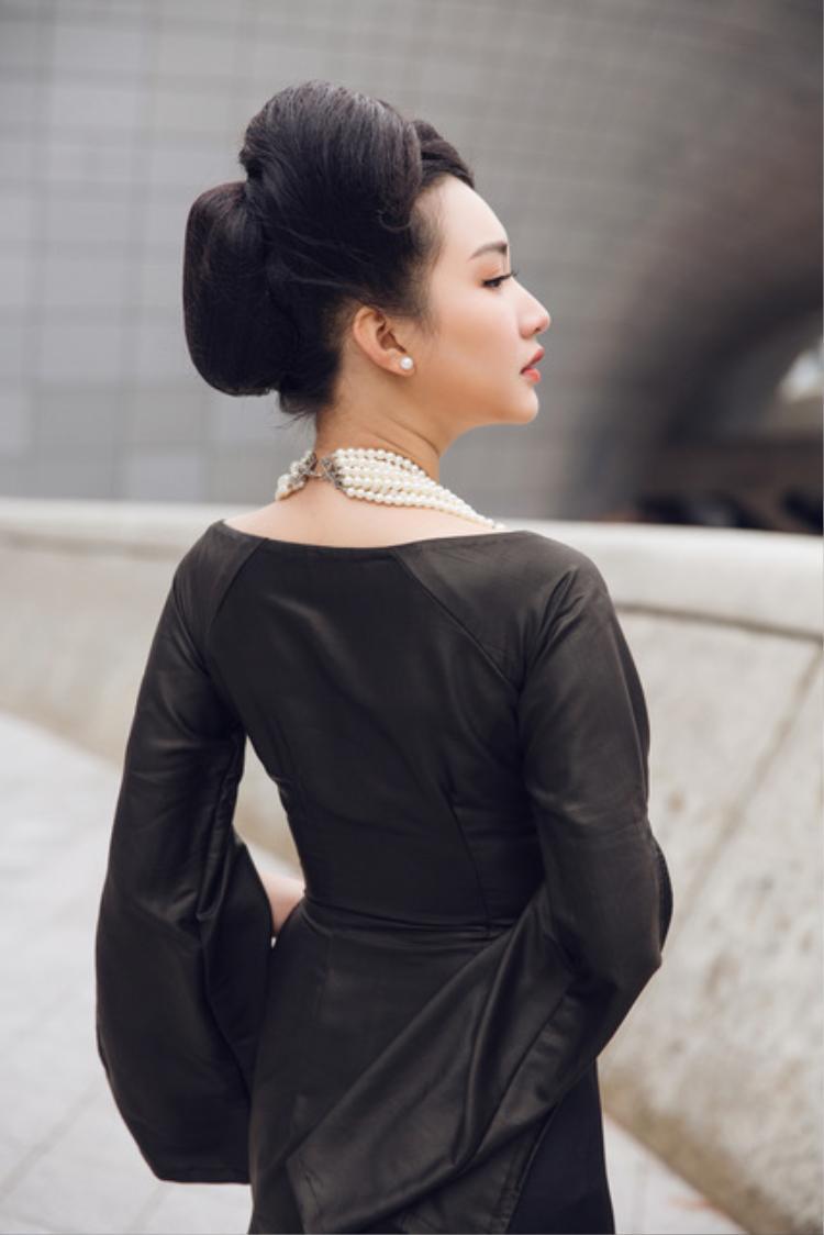 Chiếc áo dài hở phần vai khéo léo khoe được vóc dáng chuẩn cùng gương mặt đậm chất Á đông của Ngọc Trân. Người đẹp chọn cho mình kiểu tóc búi cao cổ điển chẳng khác một quý cô Sài Gòn xưa.