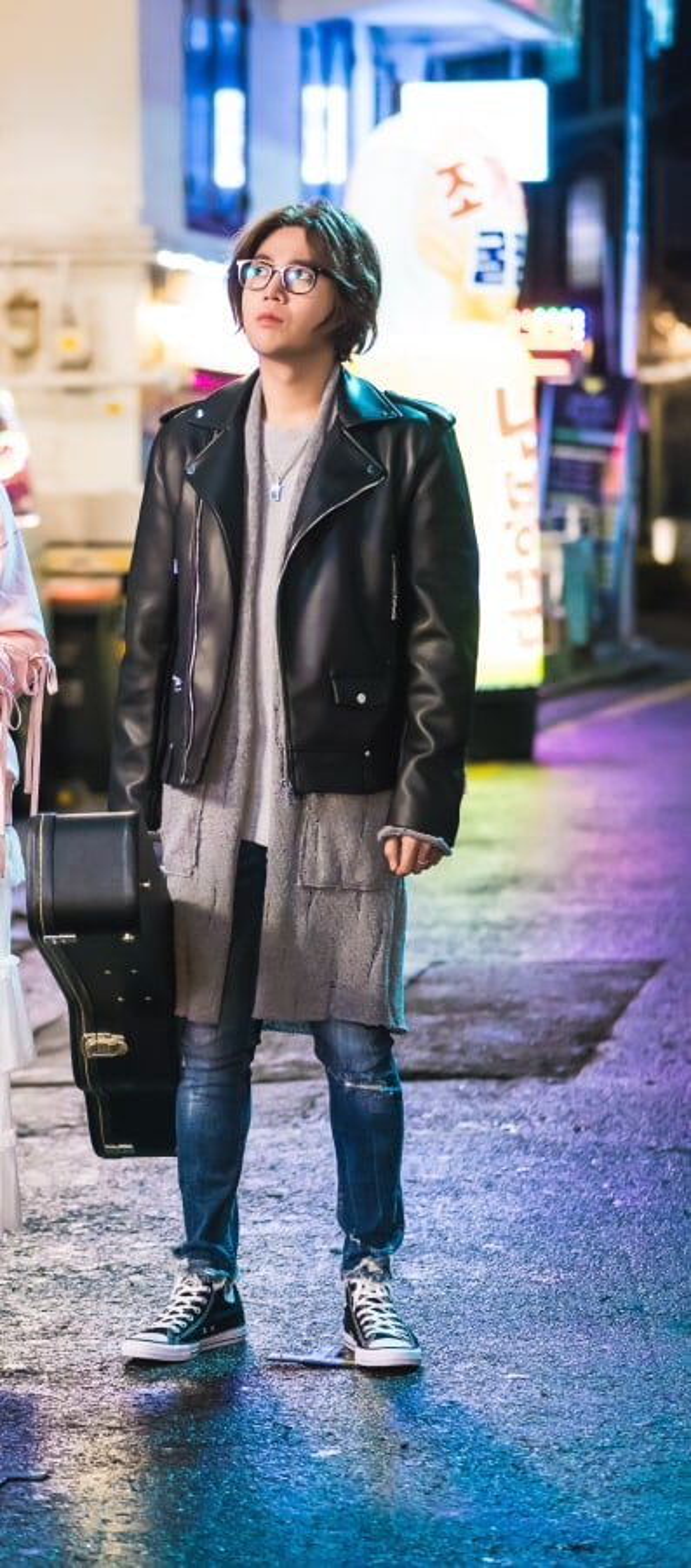 Diễn viên Cô nàng đẹp trai cố cải trang thành một nghệ sĩ đường phố, cầm một chiếc guitar đen và mặc áo khoác da với mái tóc nhuộm màu nâu.