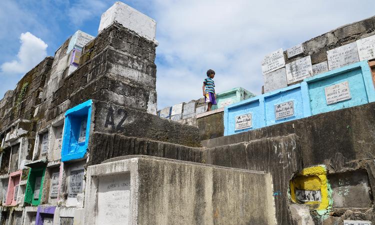 """Thủ đô Manila của Philippines là một trong những thành phố đông dân nhất thế giới do lượng người di cư từ nông thôn lên thành phố tìm kiếm cơ hội việc làm. Khi người dân ngoại tỉnh đổ về đây, phần lớn họ tự tìm nơi xây dựng thành cộng đồng riêng. Và nghĩa trang Navotas là một trong những """"khu ổ chuột"""" trú chân của những người nghèo ở thành phố này."""