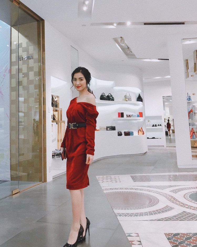 """Đầm trễ vai màu đỏ nữ tính là sự lựa chọn của Hòa Minzy khi xuống đường. Giọng ca """"Ăn gì đây"""" phối cùng thắt lưng bản to cùng giày cao gót cùng tông đen làm điểm nhấn."""