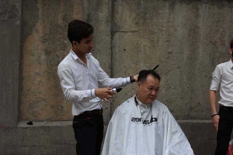 Qua đây cắt tóc, người dân được nhân viên tư vấn kiểu tóc cho phù hợp.