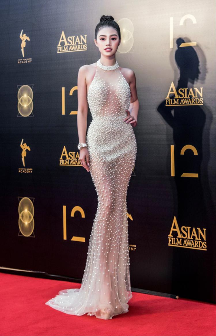 Jolie Nguyễn gợi cảm hết mức với chiếc váy ôm sát, khoe trọn vóc dáng. Các chi tiết ngọc trai được đính kết tinh tế, che những chỗ cần che khiến nàng hậu trở nên vô cùng quyến rũ, đẹp như một nữ thần trên thảm đỏ.