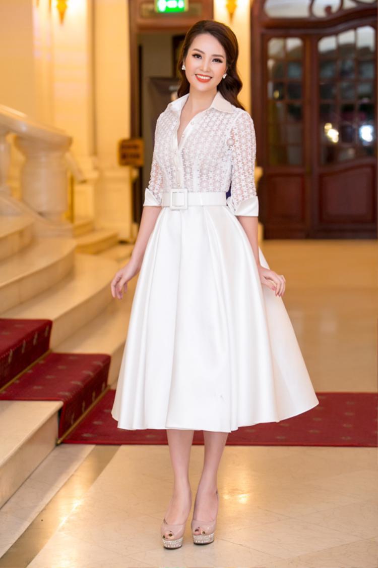 """Tham dự sự kiện, á hậu Thụy Vân chọn cho mình chiếc váy xòe bồng của NTK Quân Phan nhằm đem lại hình ảnh tao nhã, thanh lịch. Phụ kiện cũng được tiết chế, chỉ cần một đôi hoa tai là đã đủ khiến cô """"tỏa sáng""""."""