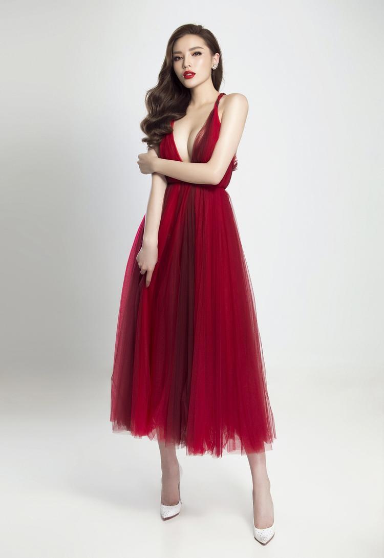 """Từng là thảm họa thời trang, tuy nhiên trong vòng hơn một năm trở lại đây phong cách của hoa hậu Kỳ Duyên đã trở nên """"cao tay"""". Chính vì vậy dù là đụng hàng đi chăng nữa nàng hậu gốc Nam Định cũng biết cách làm mình nổi bật hơn. Cụ thể nhất, trong chiếc đầm xòe với sắc đỏ gây mê hoặc, chân dài sinh năm 1995 tỏ ra biết """"dùng chiêu"""" khi khai thác tối đa lợi thế của chiếc váy."""