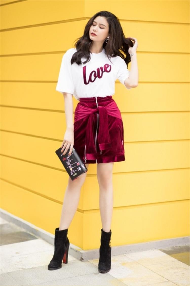 Quỳnh Anh để tóc xõa, uốn xoăn nhẹ, đi kèm là ví cầm tay. Đôi boots nhung đồng điệu với chiếc váy tạo sự hoàn hảo cho trang phục.