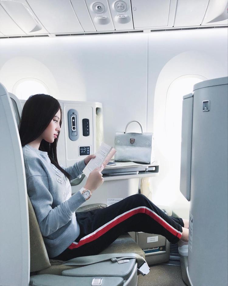 Jolie Nguyễn lựa chọn set đồ gọn gàng, giản dị gồm áo thun tay dài cùng quần nỉ sọc hai bên sườn khi đi máy bay.