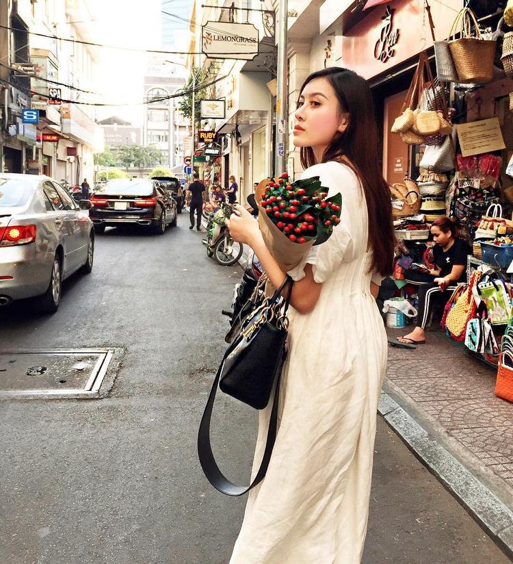 Hà Lade xinh đẹp trong chiếc đầm trắng dáng rộng nhấn eo. Cô để tóc xõa và cầm thêm túi xách hàng hiệu xuống phố.