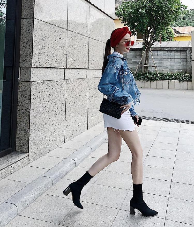 Thiều Bảo Trang xuống phố với chân váy jean trắng khoe đôi chân thon thả, đôi boots đen gót vuông góp phần tôn dáng cũng như nổi bật làn da trắng của cô.