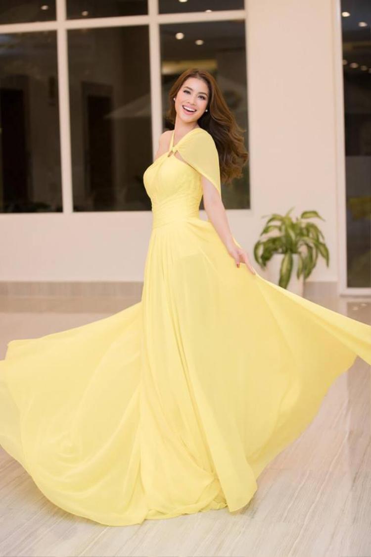 Màu sắc vàng chanh tươi trẻ cùng với chất liệu voan mỏng giúp cô trở nên nhẹ nhàng, nữ tính và mềm mại.Đặc biệt nàng hậu đã biết tương tác với váy áo để cho ra những bức hình đẹp mắt.