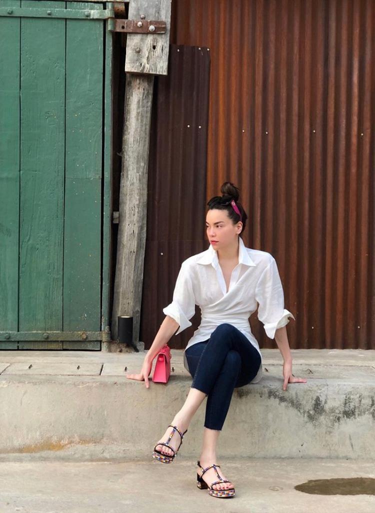 Hồ Ngọc Hà chọn sơ mi chiết eo với quần skinny giản dị. Điểm nhấn của trang phục là chiếc clutch màu hồng đắt giá và đôi sandal Gucci gắn đá nhiều màu.
