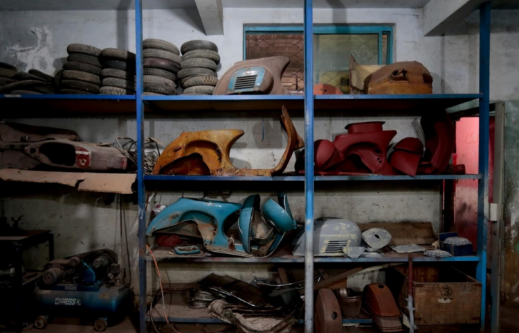 Nhiều bộ phận của xe Vespa được tháo rời và bày bán trên kệ tại một xưởng sửa chữa xe ở Islamabad.