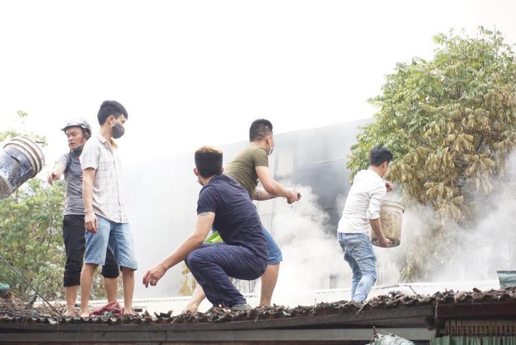 Một số người hỗ trợ lực lượng chức năng dập tắt ngọn lửa.