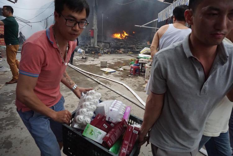 Các tiểu thương cố gắng vớt vác hàng hóa để khắc phục hậu quả vụ cháy một cách thấp nhất.