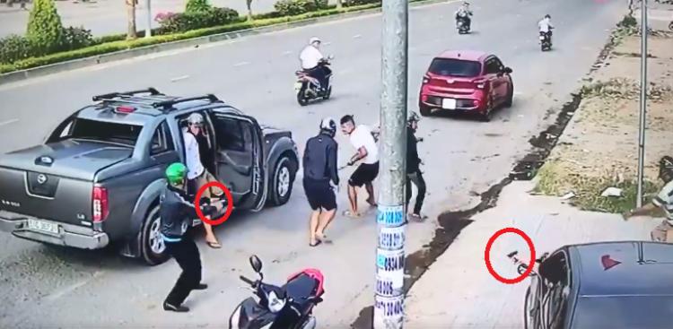 Hai người rút súng bắn trả nhóm giang hồ. Ảnh cắt từ clip.