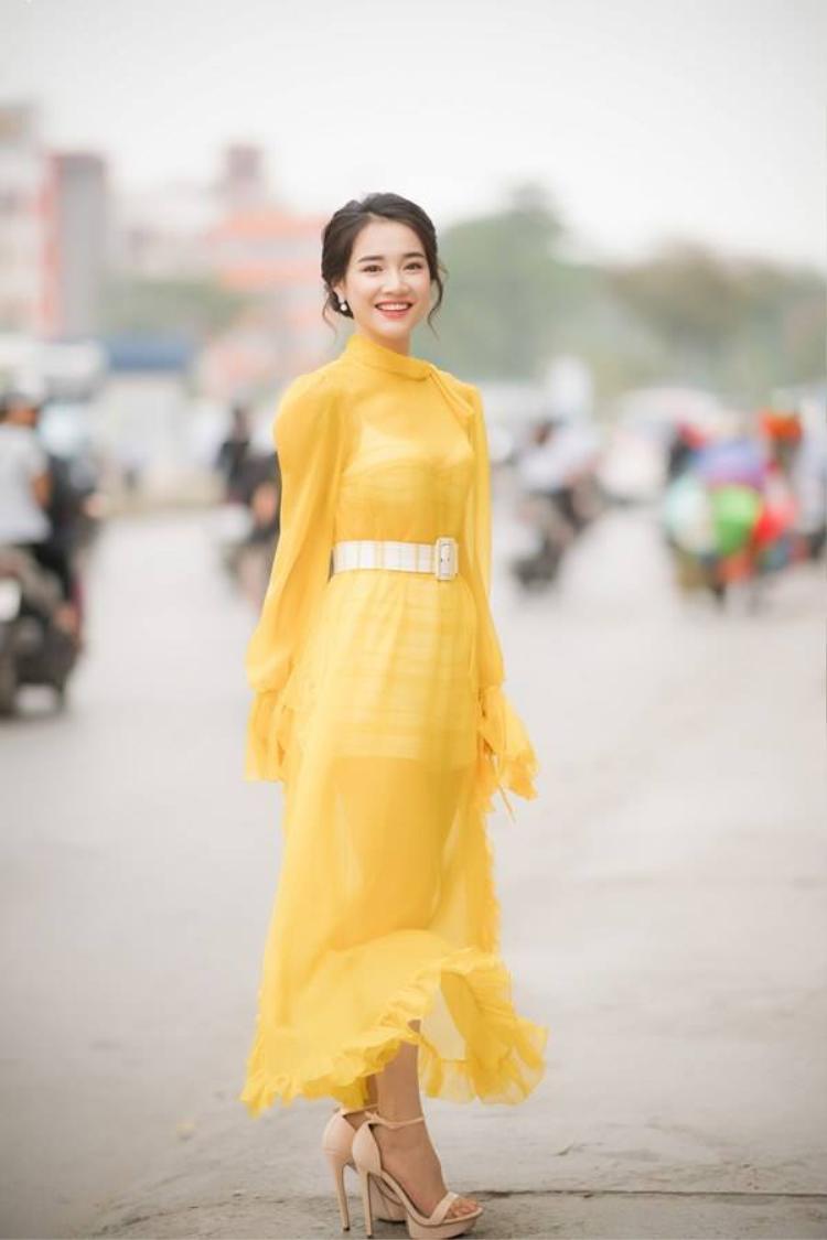 """Cô trang điểm nhẹ nhàng theo phong cách tự nhiên, điểm nhấn là màu son hồng nữ tính. Nữ diễn viên """"Tuổi thanh xuân"""" chọn cho mình chiếc váy dài, theo phong cách vintage có phần xuyên thấu khoe vóc dáng thon gọn. Màu vàng chanh làm nhiệm vụ tôn lên làn da trắng sáng của Nhã Phương."""