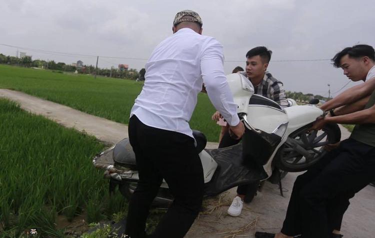 Các thanh niên giúp 2 cô nàng đưa xe máy lên bờ. Ảnh: Vũ Đắc Nhiệm.