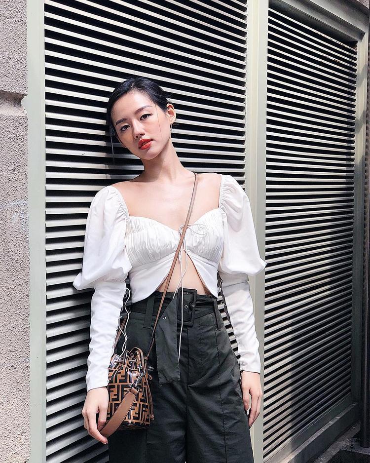 Với chiếc áo croptop thiết kế lạ mắt, Khánh Linh The Face mix cùng quần ống suông đen và sử dụng túi đeo chéo Fendi làm điểm nhấn.