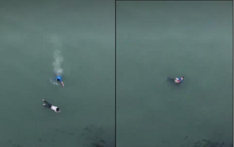 Nam thanh niên áo xanh nhảy xuống sông cứu cô gái trẻ. Ảnh cắt từ clip.