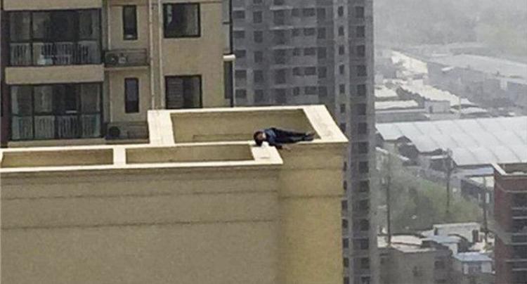 Người đàn ông nằm chênh vênh trên tường của tòa nhà cao 29 tầng. Ảnh Shanghaiist