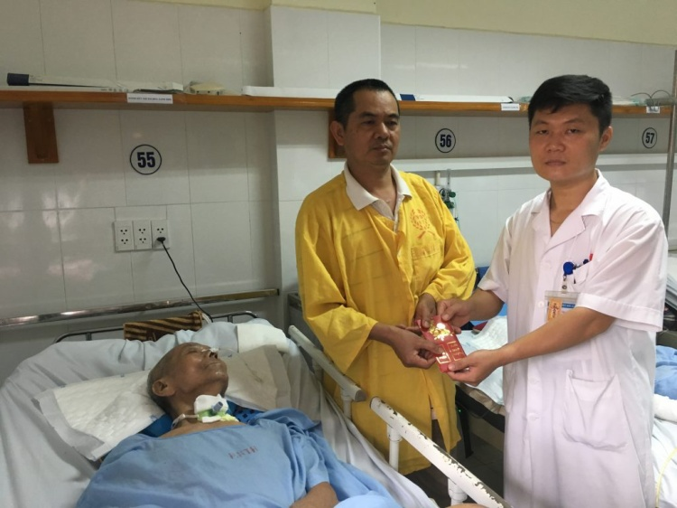 Đại diện Khoa Phẫu thuật Thần kinh II Bệnh viện HN Việt Đức trao phần quà của các nhà hảo tâm đến gia đình bệnh nhân Nguyễn Duy Hồng