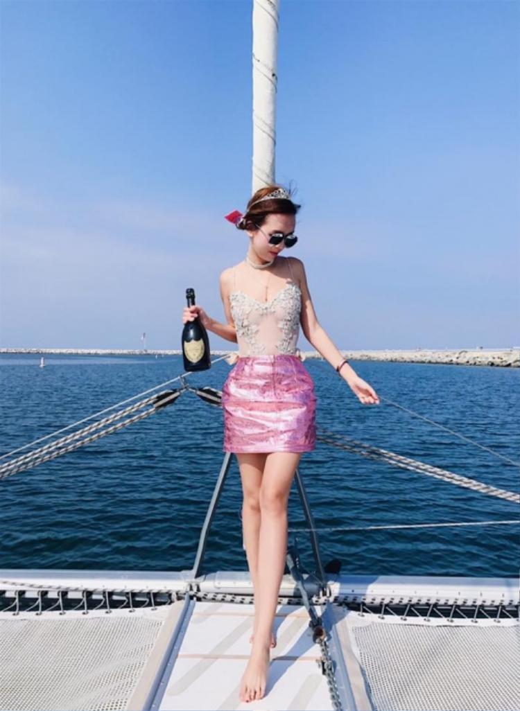 Thả dáng trên du thuyền nhưng cô nàng vẫn không quên điệu đà một chút với áo ren, chân váy hồng búp bê và vương miện công chúa.
