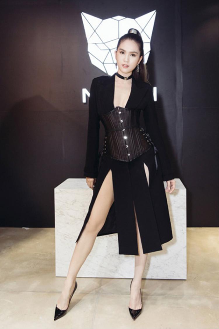 Ngọc Trinh cá tính khi theo đuổi hình tượng chiến binh cùng áo corset đen phối với chân váy xẻ. Kiểu tóc cột cao, giày cao gót cùng vòng cổ choker giúp người đẹp gốc Trà Vinh hoàn thiện tổng thể.