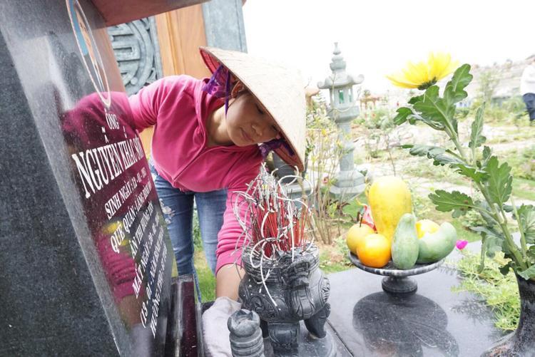 Trong ảnh chị Hảo đang lau dọn phần mộ cho gia đình.