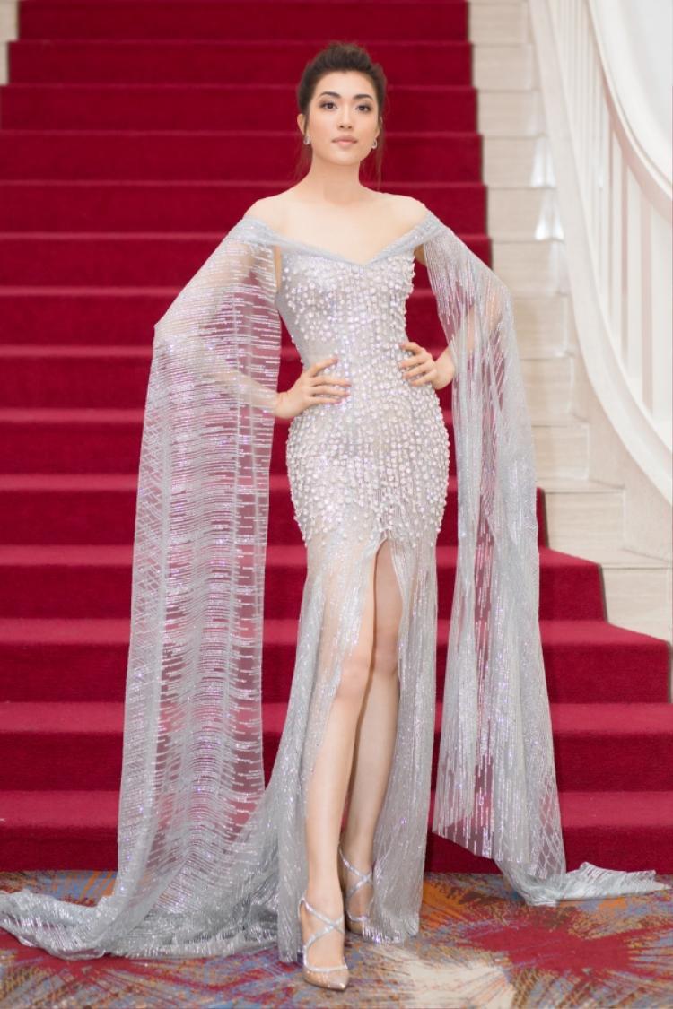 Á hậu Lệ Hằng xinh đẹp như nữ thần khi diện váy đuôi cá màu bạc với phần tay áo dài chấm đất.
