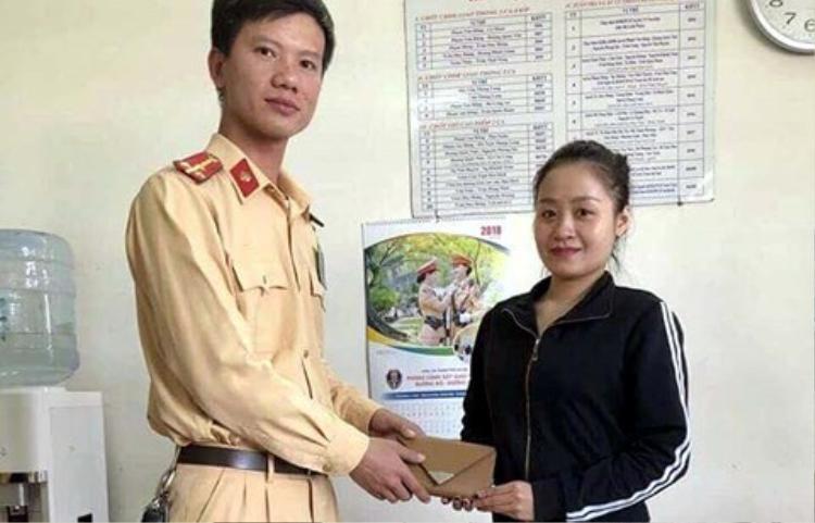 Chiến sĩ CSGT trao ví cho cô gái. Ảnh: Infornet.