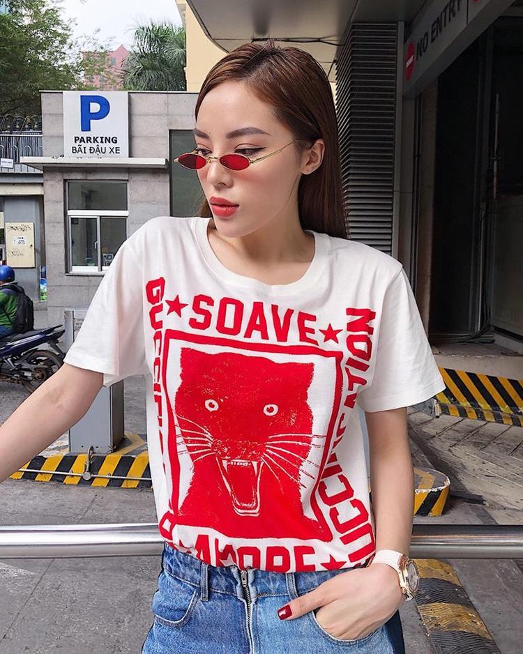 Áo thun trắng, họa tiết và slogan đỏ của Gucci đang được các sao rất yêu thích. Kỳ Duyên đã nhanh tay sắm một chiếc và kết hợp với quần jeans đơn giản. Cặp kính Gentle Monster tiệp màu khiến outfit của nàng hậu nổi bật hơn hẳn.