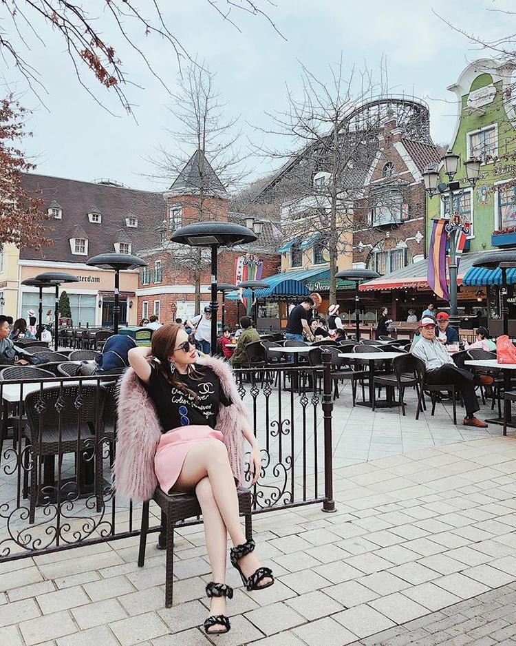 Diện áo thun đen của Chanel, Bảo Thy kết hợp với áo khoác lông màu hồng và chân váy cũng màu hồng cùng đôi sandal đan dây lạ mắt.