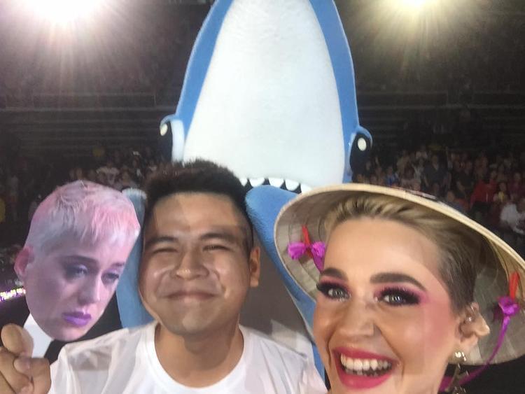 """Katy Perry đội nón lá truyền thống của Việt Nam và selfie với người hâm mộ may mắn nhất đêm. Chính anh chàng này là người đã """"dụ dỗ"""" Katy đến Việt Nam thành công. (Nguồn ảnh: Fanpage Katy Perry Vietnam)."""