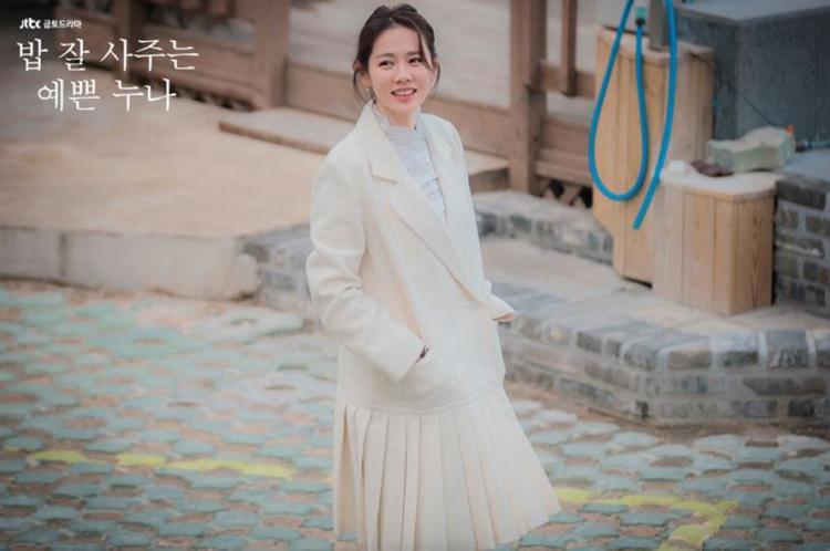 """Mẫu áo khoác được may cách điệu thành váy rất phù hợp với áo sơ mi cổ ren màu trắng bên trong. Kết hợp cả ren, bèo nhún và xếp pli nhưng tạo hình này không hề bị """"sến"""" hay gây rối mắt."""