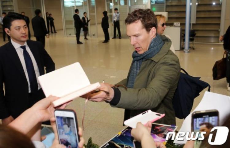 Nam diễn viên vui vẻ ký tặng người hâm mộ.