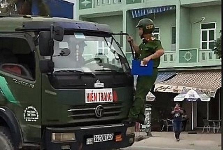 Chiến sĩ công an bám gương yêu cầu tài xế dừng xe. Ảnh cắt từ clip.