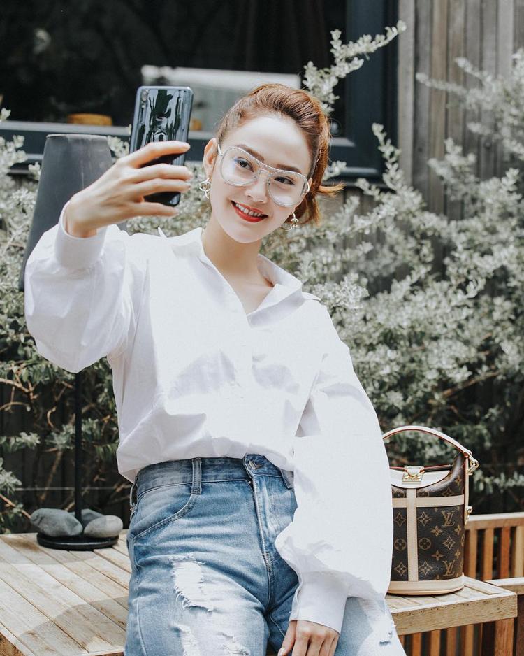 Thay vì sơ mi trắng đơn giản, Minh Hằng chọn kiểu áo tay bồng, tạo vẻ khác lạ, phía xa xa là sự xuất hiện của chiếc túi Sac Duffle đắt đỏ đang được nhiều tín đồ thời trang mê mẩn giá trị lên đến 2.280 USD - hơn 50 triệu đồng.