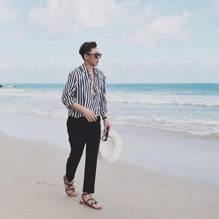 Hoàng Ku trông lịch lãm nhưng vẫn trẻ trung khi diện áo sơ mi sọc cùng quần skinny jeans dạo biển.
