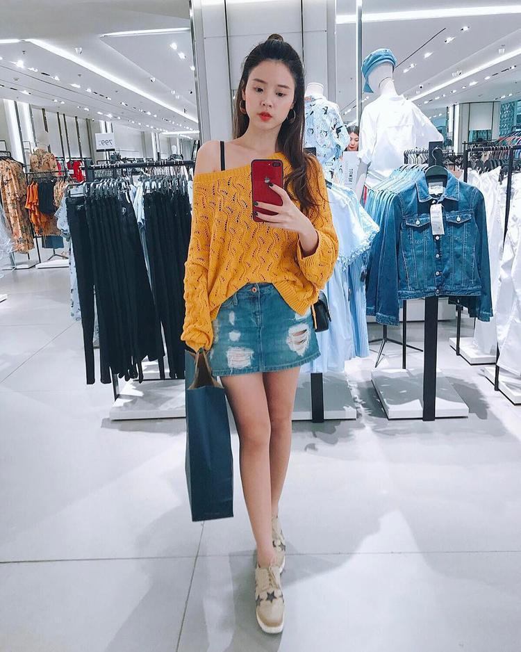 """Bắt nhịp xu hướng màu vàng của mùa hè năm nay, Midu đem đến set đồ trẻ trung gồm áo dệt kim lệch vai cùng chân váy jeans ôm. Kiểu tóc bới """"củ tỏi"""" cũng giúp tôn lên khuôn mặt trái xoan xinh xắn của người đẹp."""