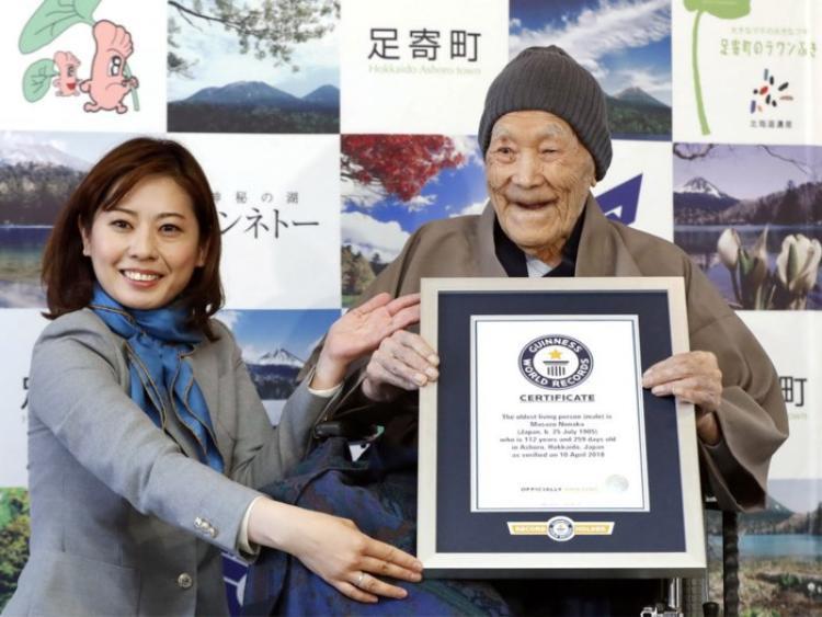 Đại diệntổ chức Guinness trao giấy chứng nhận kỷ lục thế giới cho cụ Nonaka. Ảnh: AFP