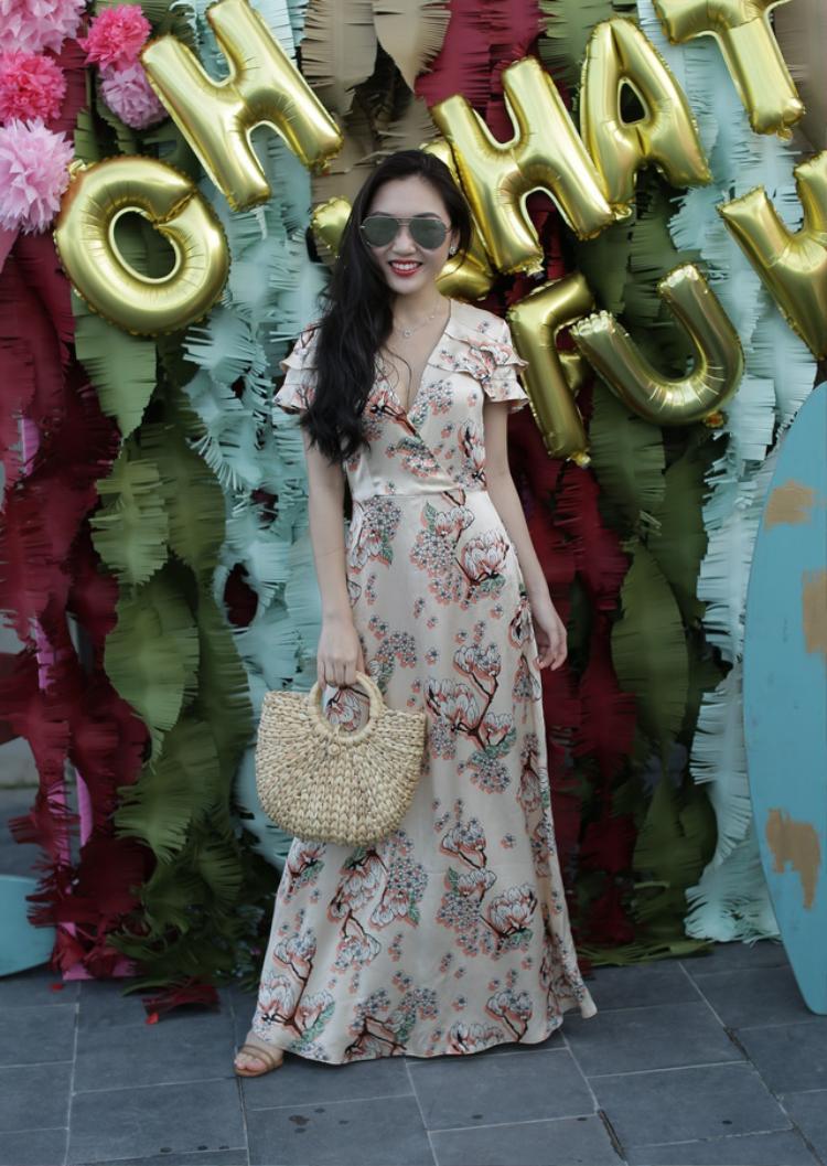 """Beauty blogger Chloe Nguyễn bắt kịp xu hướng với đầm hoa cổ đắp và túi cói """"ăn rơ"""" với bộ đầm đậm chất mùa hè này."""