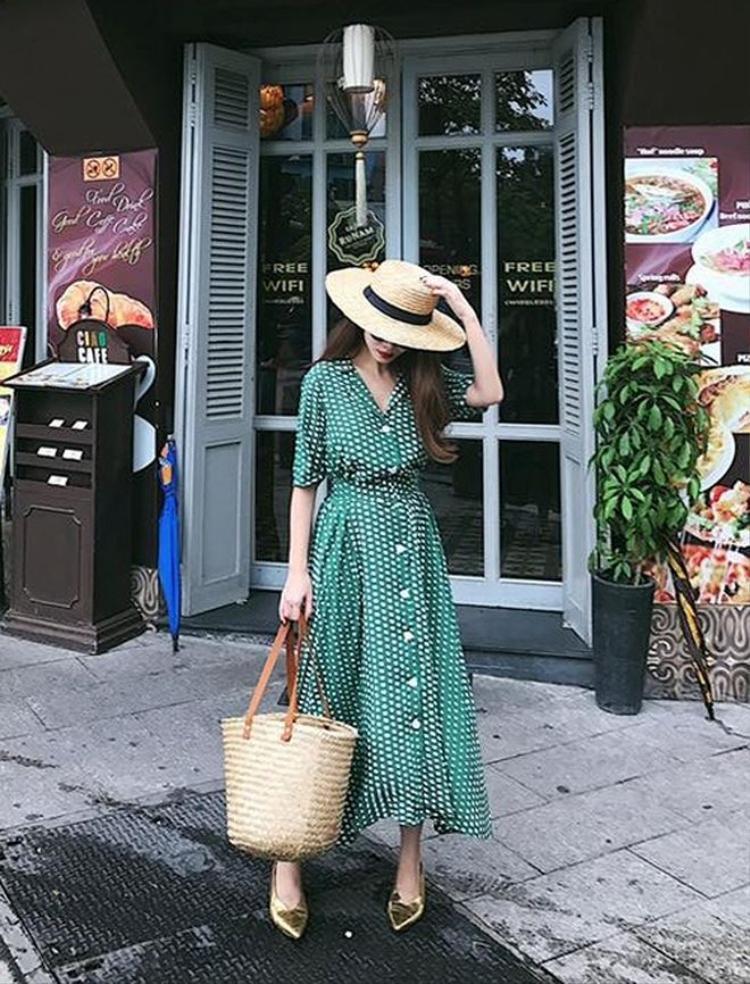 """Ca sĩ Yến Nhi nghiêng hẳn về phong cách """"đồng quê"""" khi diện đầm chấm bi cùng với túi cói big-size."""
